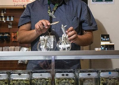 Digital 303 Marijuana Photographer: Budtender Selling Cannabis Products